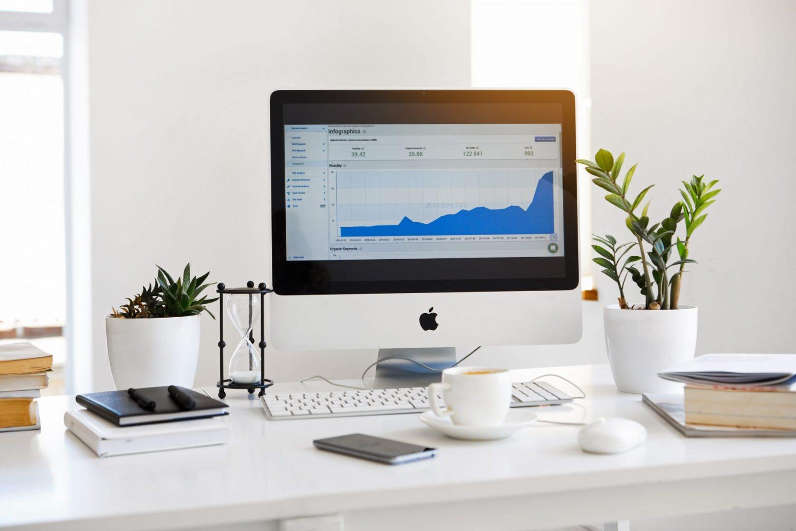 Biurko, na którym stoi monitor marki APPLE