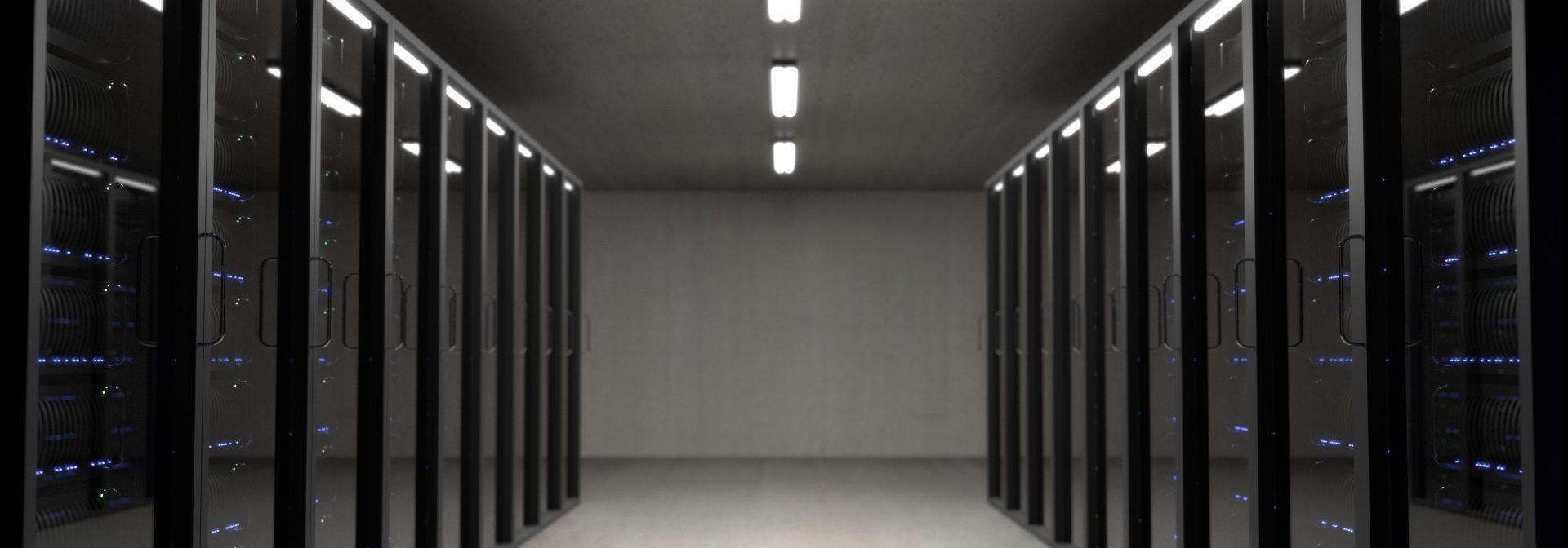 Serwerownia, korytarz, szafy serwerowe po lewej i prawej stronie