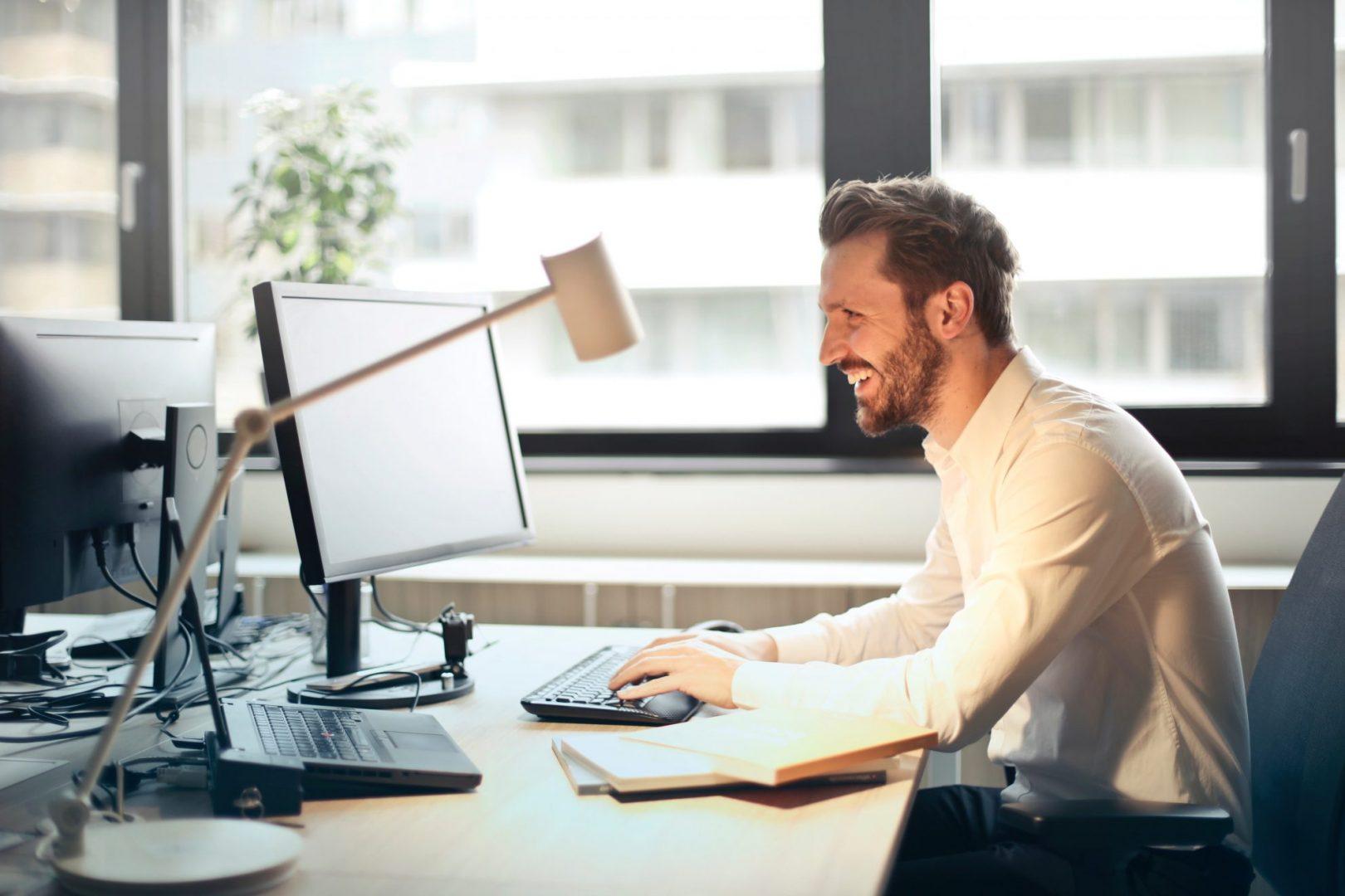 Usmiechniety mezczyzna siedzacy przy komputerze